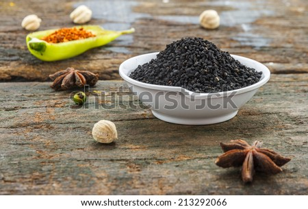 The nigella seed on wood texture for design or decorate project. - stock photo