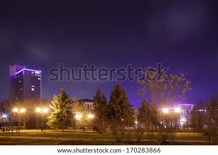 the night city with trees parks and by passing cars - stock photo