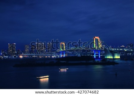 The night view of the Tokyo Rainbow Bridge and Tokyo Tower under a blue evening sky. Photoed at Odaiba, Tokyo, Japan. - stock photo
