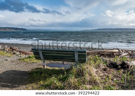 The normally placid Puget Sound is filled with whitewater on a windy day. Bench in the foreground. - stock photo
