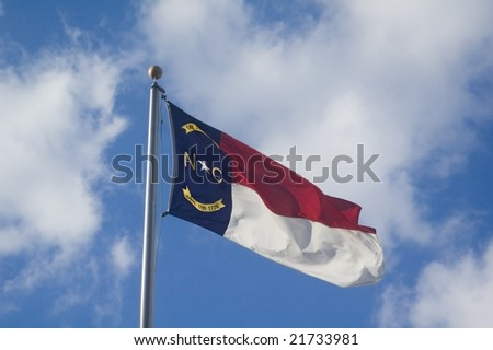 The North Carolina State flag flying on a sunny day