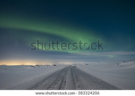 The northern lights dancing in the sky above a frozen mountain road - stock photo