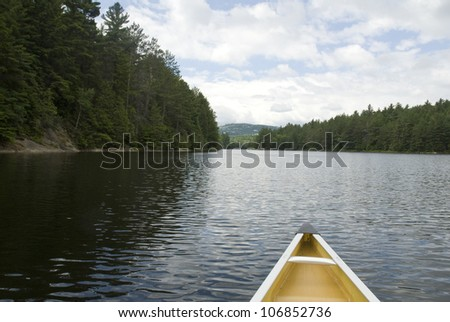 The nose of a canoe points the way into a distant passage in a wilderness lake.