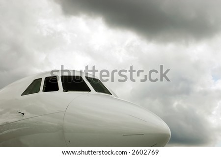 The nose of a white jet plane under stormy skies - stock photo