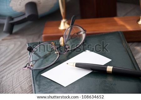 The notebook and glasses with the pen lays on a grey background - stock photo