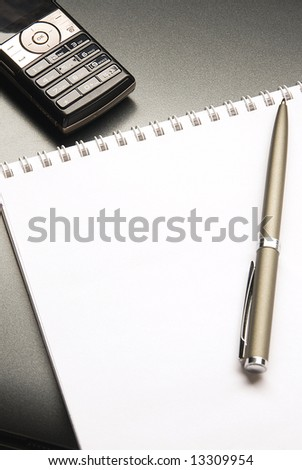 The notebook and mobile phone with the pen lays on a grey background - stock photo