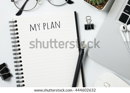 The notebook page is open on the white desk table with laptop and supplies. Life/Business planning concept. - stock photo