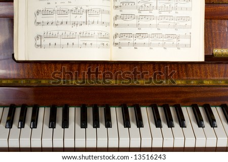 The notebook with notes lays on the piano - stock photo