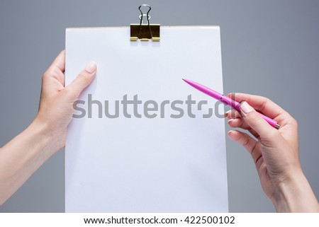 The notepad and pen in female hands - stock photo