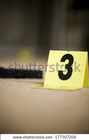the number 3 at a crime scene with a gun blurred in the background. - stock photo