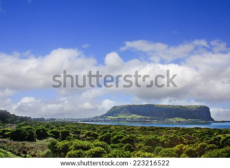 The Nut is a 152 metre high geological feature, the core of an extinct volcano, looming above the village of Stanley - stock photo