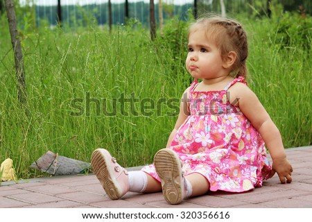 The offended little girl with pouting lips sitting on the ground, summer outdoor - stock photo