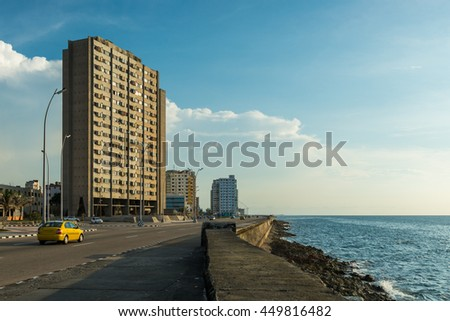 The old architecture of Havana, Cuba, stands across from the Malecon, a long boardwalk that runs along the Caribbean sea.