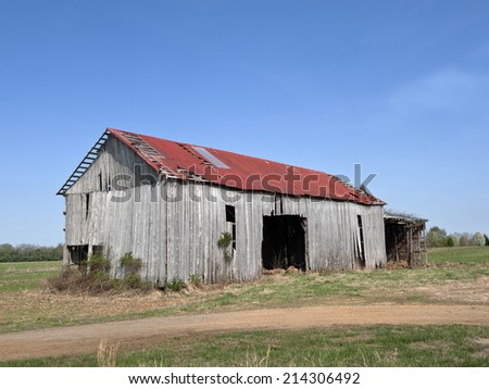 The old barn sits abandoned. - stock photo