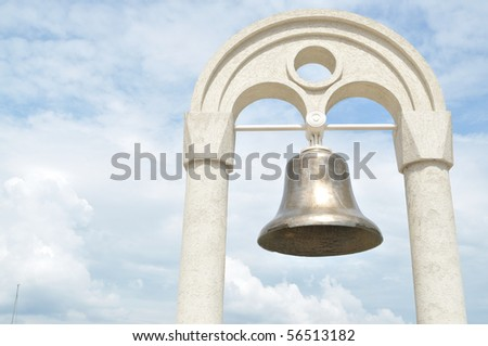 The old bell in the background of the sky,hanging on the arch - stock photo