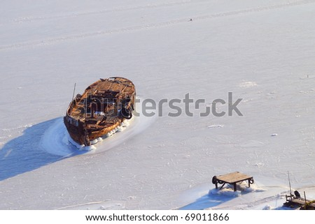 The old boat is frozen into the ice near the old wooden pier - stock photo