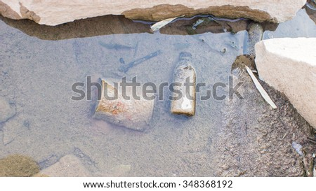 The old canned garbage under the water - stock photo