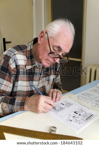 The old cartoonist is drawing the cartoons. - stock photo