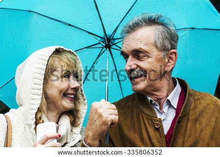 The old couple in the rain with umbrellas  - stock photo