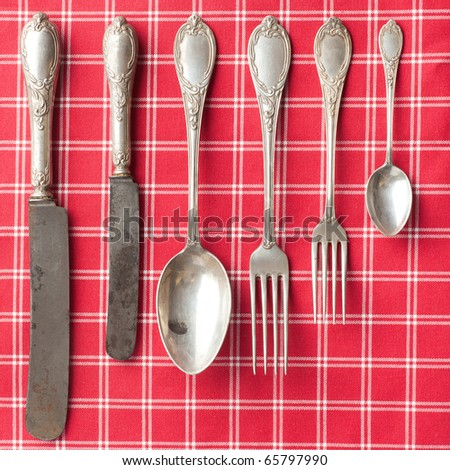 the old cutlery on checkered tablecloth - stock photo