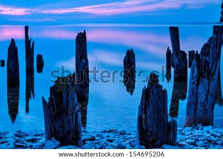 The Old Dock. Old dock pilings lit by the summer sun. Fayette State Park. Fayette Michigan. - stock photo