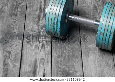 The old dumbbell on the wooden floor - stock photo