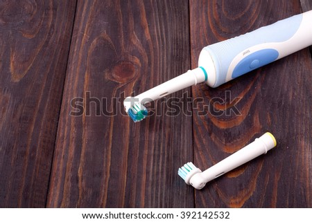 The old electric toothbrush on wooden background - stock photo