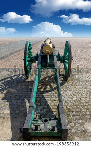 The old fashioned cannon on a square over blue sky