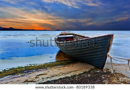 The old fishing boat at sunset - stock photo