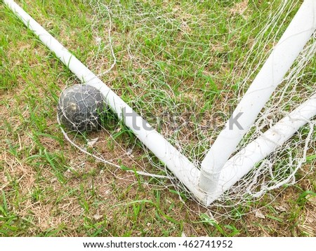 The old football in the goal net on the grass field.
