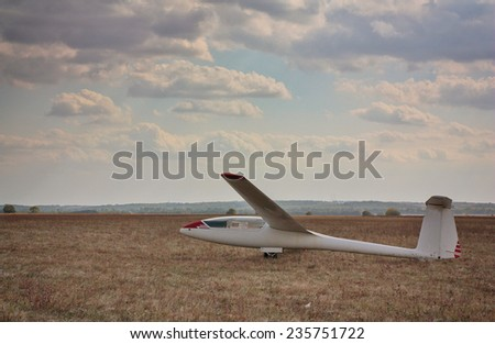 The old glider against the cloudy sky - stock photo