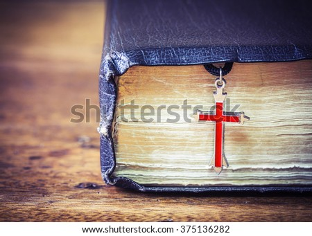 The old holy bible with  metal res cross on wooden background - stock photo