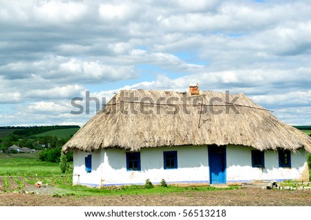 The old house with a thatched roof - stock photo