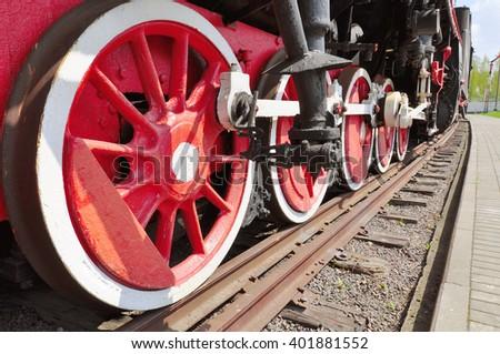 The old iron railway locomotive red wheels. - stock photo