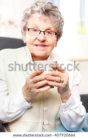 The old lady drinking a brew of herbs. Mature woman resting on a chair with a cup of brew with herbs