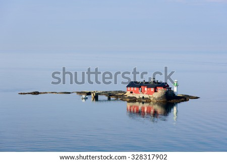 The old lighthouse of Botto. A red house on a very small rocky island serving as lighthouse. A remote island in a calm sea. Blue sky and morning sunlight. A small white motorboat moored at the island. - stock photo