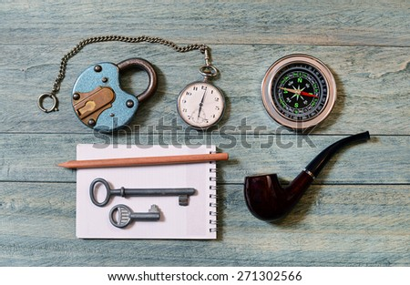 The old lock, pocket watch and compass on the table - stock photo
