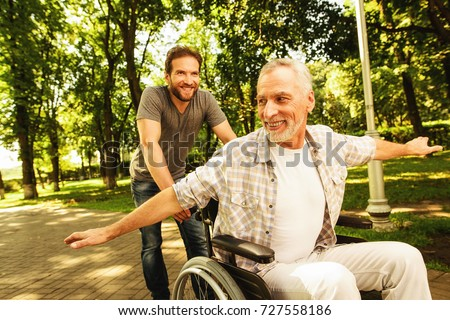 The old man on a wheelchair is walking in the park with his adult son. They fool around and laughing. They are having fun