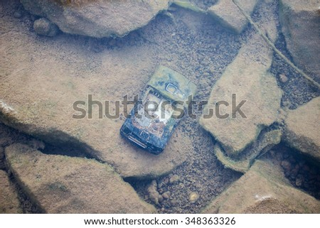 The old mobile phone garbage under the water - stock photo