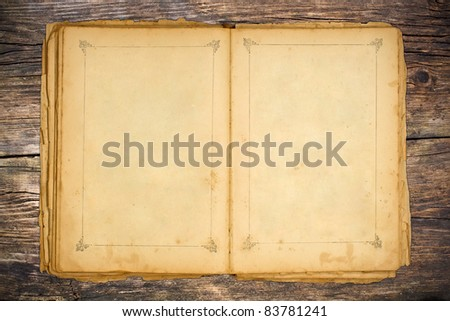 The old open book on wooden table - stock photo