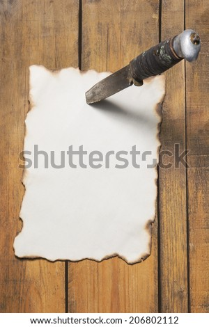 The old paper pinned to a wooden wall by knife - stock photo