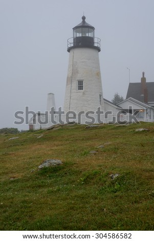 The old Pemaquid Lighthouse enveloped in heavy fog sits on the edge of the Atlantic Ocean on the Maine Coast early morning - stock photo