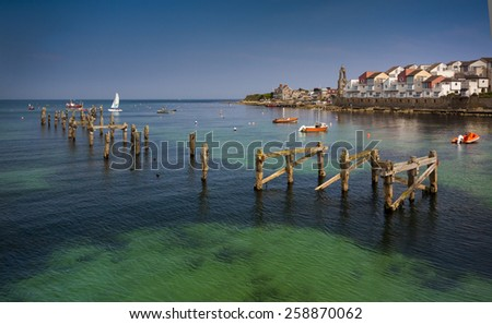 The old pier posts can be seen in the blue-green waters under the new houses perched on the seafront - stock photo