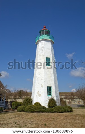 The Old Point Comfort lighthouse, a part of the new Fort Monroe National Monument, in winter against a bright blue sky - stock photo