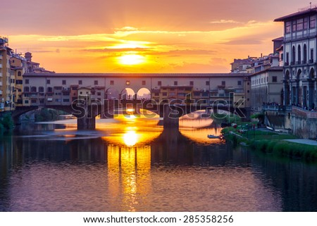 The old Ponte Vecchio over the Arno River in Florence at sunset. - stock photo