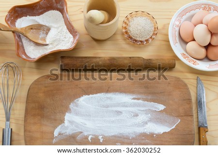 The old rolling pin and a wooden cutting Board with flour, chicken eggs, whisk, knife and mortar with pestle on wooden table