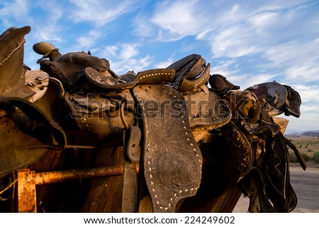 The old saddles as the sun sets in the country. - stock photo