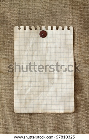 The old sheet of paper is pinned by the old drawing-pin to an old fabric - stock photo