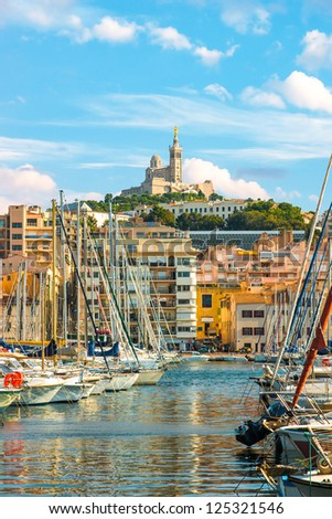 The old Vieux port of Marseille with Notre Dame de la Garde at back - stock photo