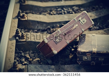 The old vintage suitcases forgotten lie on railway rails.